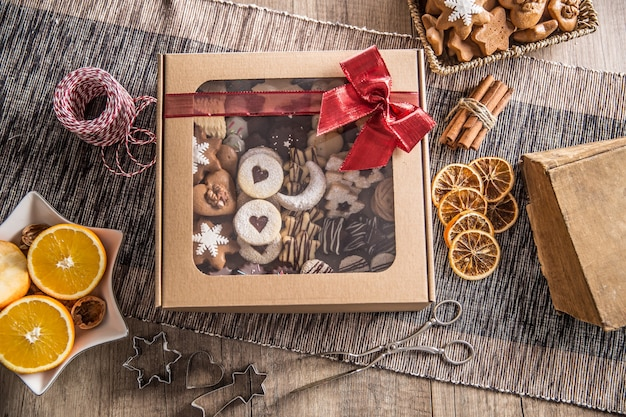 Schachtel voller weihnachtlicher süßer cokies und gebäck mit rotem band.