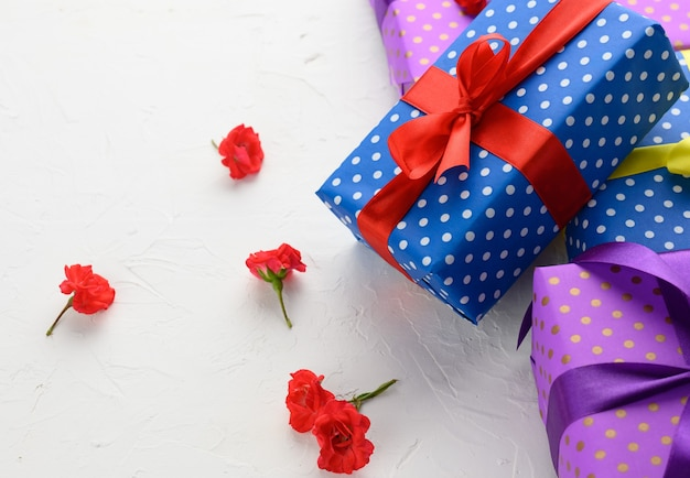 Schachteln in festlichem blauem papier verpackt und mit seidenband auf weißem hintergrund gebunden, geburtstagsgeschenk, überraschung