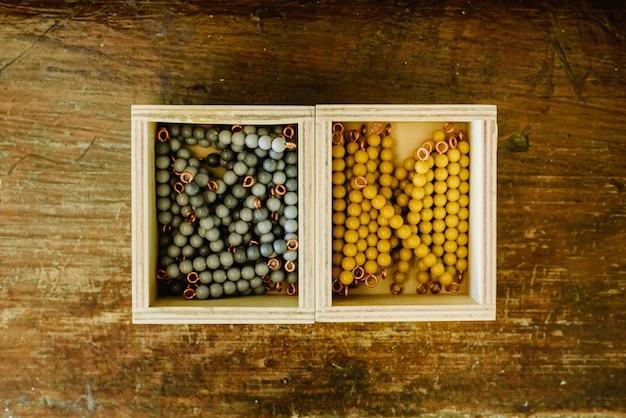 Schachteln mit perlen zum zählen in einem montessori-klassenzimmer auf altem holz.