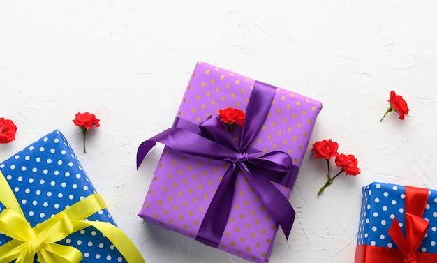 Schachteln sind in weihnachtspapier mit tupfen verpackt und mit einem seidenband auf einem hintergrund gebunden, geburtstagsgeschenk, überraschung