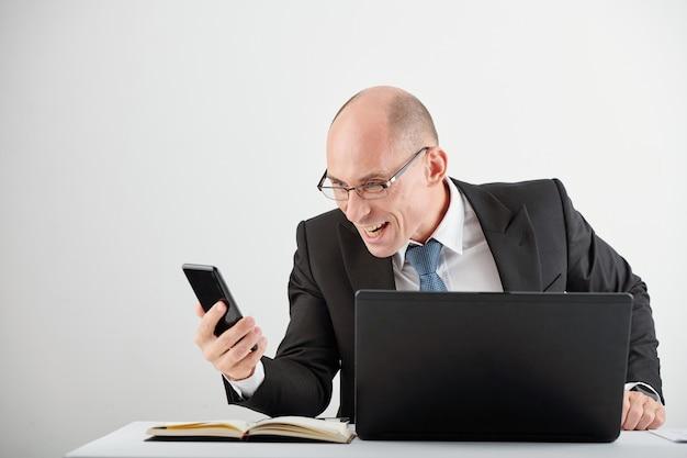 Schadenfreude geschäftsmann mit brille, der am schreibtisch mit geöffnetem laptop sitzt und nachrichten über das scheitern von geschäftsrivalen liest