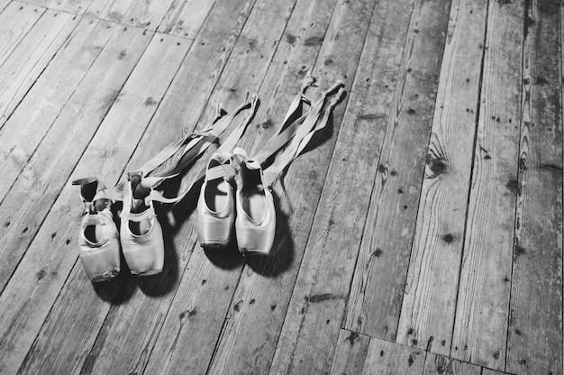 Schäbige ballettpointenahaufnahme auf einem hölzernen hintergrund