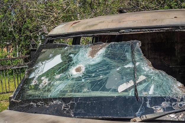 Schäbiges verwittertes auto mit zerbrochenem panzerglas nach dem schießen.