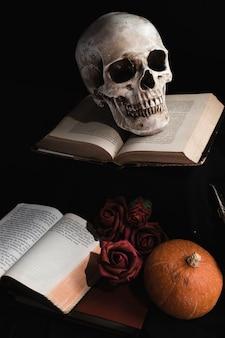 Schädel auf büchern mit rosen und kürbis
