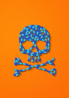 Schädel aus blauen kapselpillen isoliert auf orange. 3d-illustration