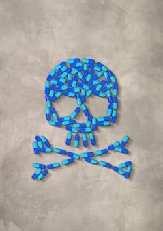 Schädel aus blauen kapselpillen lokalisiert auf betonhintergrund. 3d-illustration