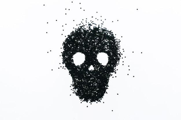 Schädel bestehend aus schwarzem konfetti in form von sternen auf weißem hintergrund halloween-konzept