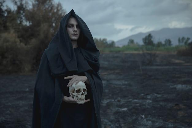 Schädel, der vom männlichen magier in der schwarzen kleidung gehalten wird