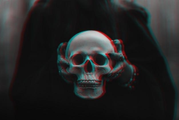 Schädel eines toten mannes in den händen einer hexenhexe in einem schwarzen kostüm für ein okkultes satanisches ritual. schwarzweiß mit 3d-glitch-virtual-reality-effekt