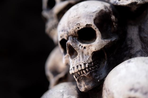 Schädel-halloween-hintergrund viele leute-schädel stehen übereinander. mystisches gruseliges konzept. abstraktes okkultes denkmal des albtraums.