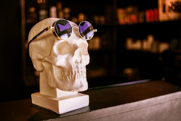Schädel in der sonnenbrille ist auf dem regal. nahansicht