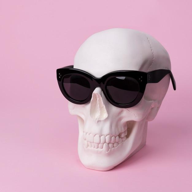 Schädel in sonnenbrille auf pastellrosa tisch.