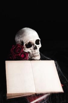 Schädel mit buchmodell auf schwarzem hintergrund