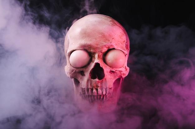 Schädel mit gespenstischen augäpfeln in rauch
