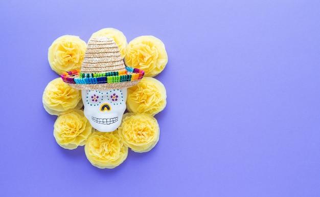 Schädel mit mexikanischem hut umgeben von gelben blumen.