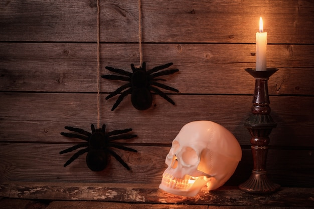 Schädel und kerze auf hölzernem hintergrund. halloween