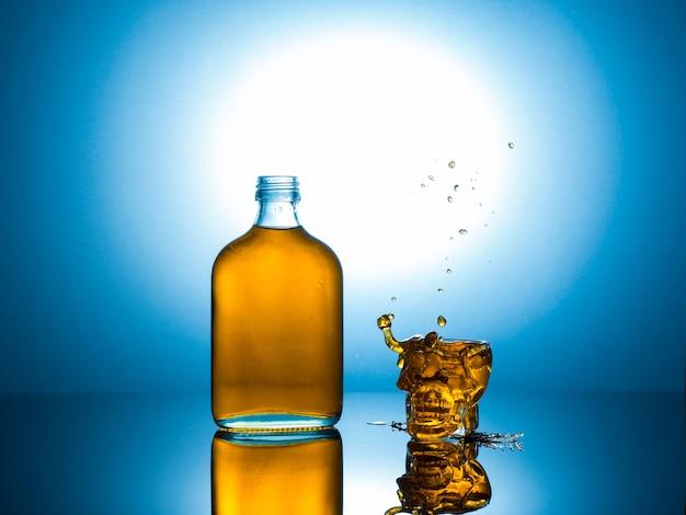 Schädelglas mit flacher flasche auf reflexionsmasse.