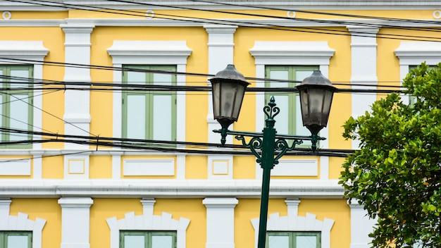 Schädigende weinlesestraßenlaternefront das gelbe antike gebäude