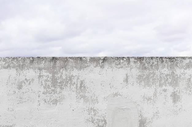 Schädigender zementwandhintergrund und dicker himmel