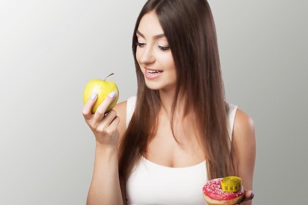 Schädliche und gesunde ernährung junges mädchen wählt zwischen schädlicher und gesunder ernährung diätkonzept von gesundheit und schönheit.