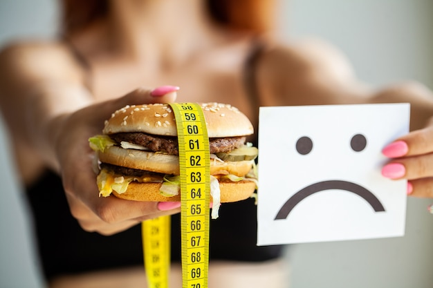 Schädliches essen. die wahl zwischen bösartigem essen und sport. schönes junges mädchen auf diät. das konzept von schönheit und gesundheit.