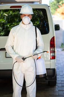 Schädlingsbekämpfungsmann, der nahe bei einem packwagen steht