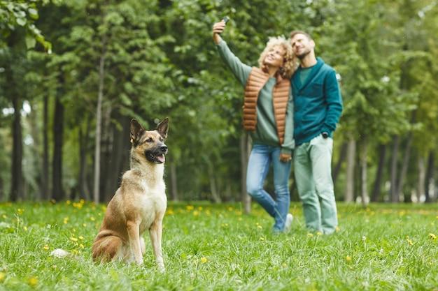 Schäferhund, der auf dem grünen gras mit dem jungen paar sitzt, das im hintergrund im hintergrund selfie macht