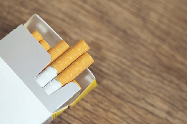 Schälen sie es ab zigarettenpackung bereiten das rauchen vor. packaufstellung auf den holztisch gestellt. fotofilter natürliches licht.