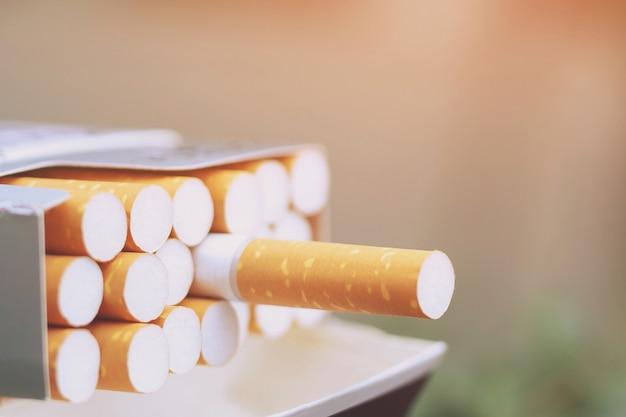 Schälen sie es von der zigarettenschachtel. bereiten sie das rauchen einer zigarette vor. verpackungslinie.