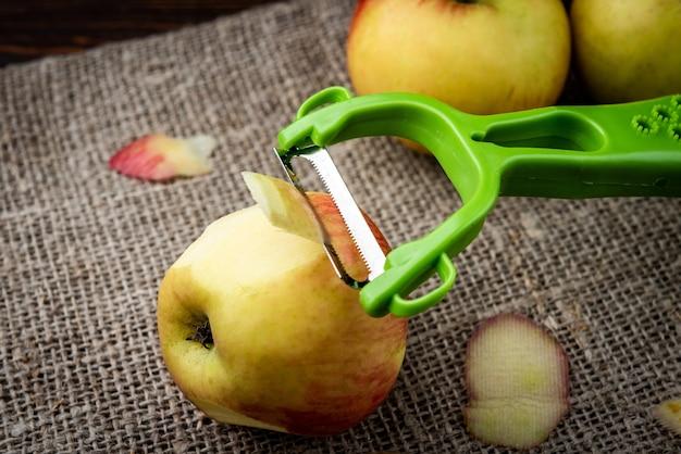 Schälmesser und äpfel auf dunkler holzoberfläche.