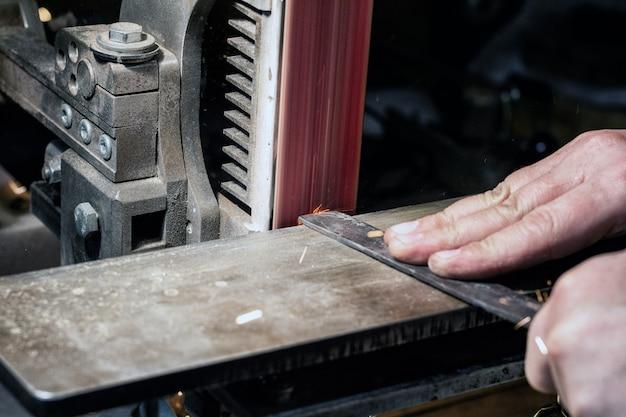 Schärfen der klinge bei einem bandschleifer. messer machen meisterhände nah.
