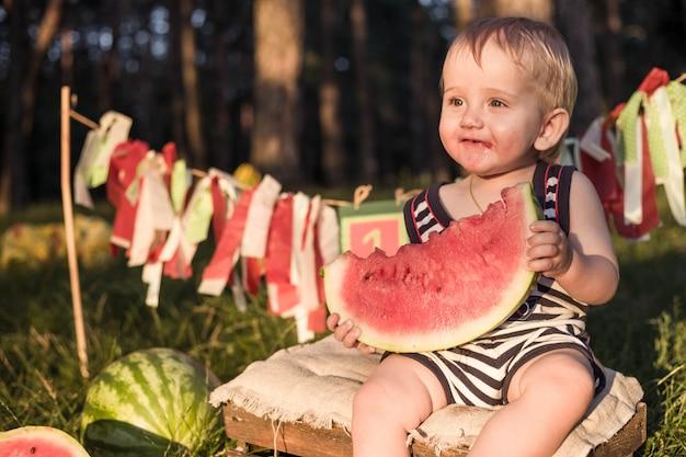 Schätzchenblonder junge essen wassermelone und lächeln.