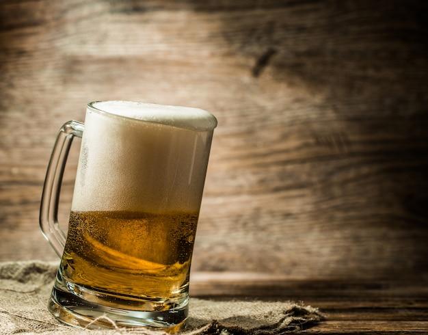 Schäumendes bier goss in den becher, der auf tabelle steht