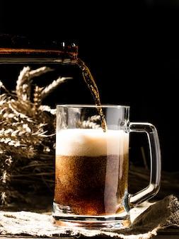 Schäumendes bier lief in den becher ein, der auf leerem hölzernem hintergrund steht