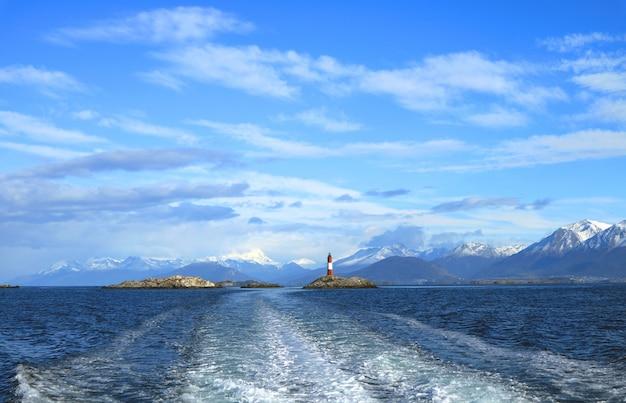 Schäumendes wasser am heck des kreuzschiffs mit leuchtturm, spürhundkanal, ushuaia, argentinien