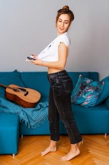 Schaffung. künstlerin musiker in der kreativen suche. steht mit einer gitarre neben dem sofa. mit farbe befleckt.