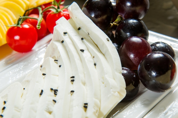 Schafskäse mit basilikum und schwarzen oliven, tomaten auf schneidebrett, isoliert auf weiß