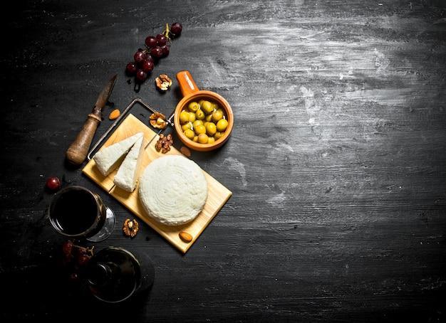 Schafskäse mit rotwein, nüssen und oliven.