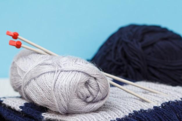 Schal und garnstränge mit metallstricknadeln auf grauen brettern und blauem hintergrund. strickkonzept. geringe schärfentiefe.