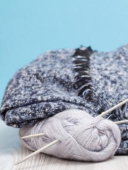 Schal und garnstränge mit metallstricknadeln auf grauen brettern und blauem hintergrund. strickkonzept.