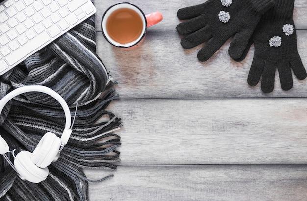 Schal und handschuhe in der nähe von tee und geräten