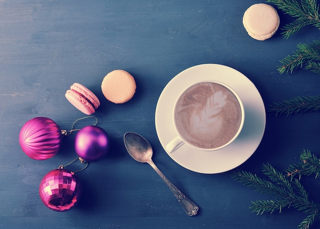 Schale cappuccino mit kuchen macaron, weihnachtsspielwaren
