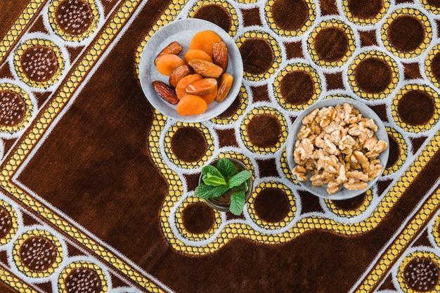 Schale des getränks nahe trockenfrüchten und nüssen auf matte