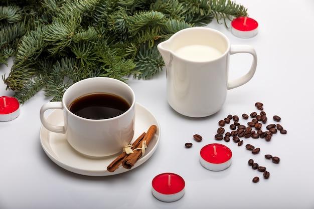 Schale espresso mit milch, zimtstangen, tannenbäumen, roten kerzen und auf einem weißen hintergrund