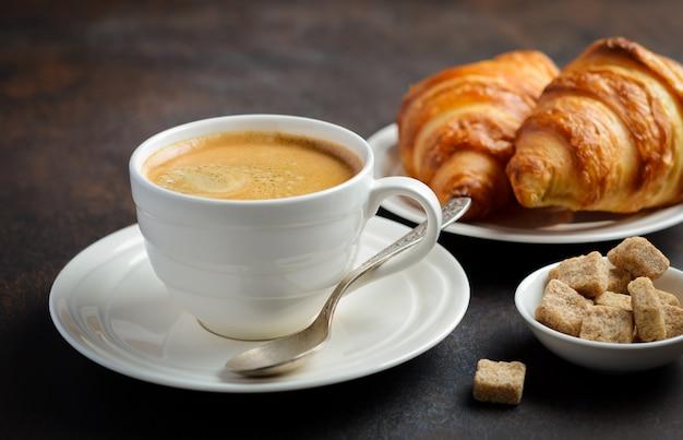 Schale frischer kaffee mit hörnchen auf dunklem hintergrund.