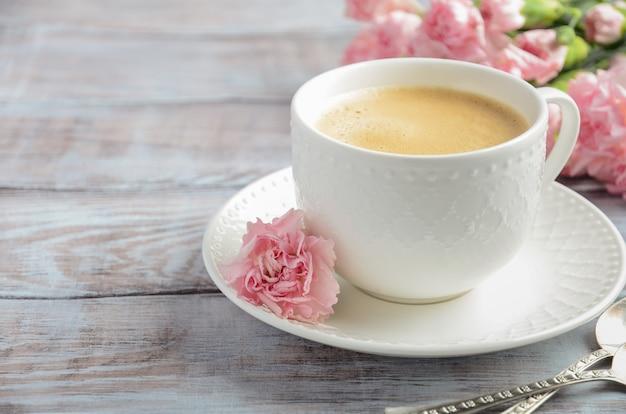 Schale frischer morgenkaffee mit rosa gartennelkenblumen. valentinstag-konzept.