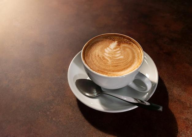 Schale heiße lattekunst im nachmittagslicht auf holztisch