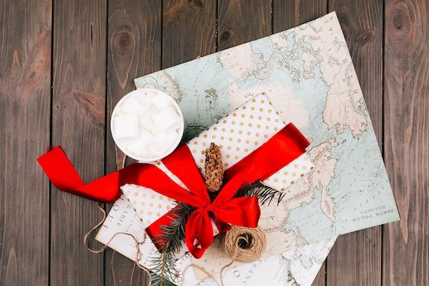 Schale heiße schokolade mit eibischen steht vor rotem präsentkarton auf weißer karte