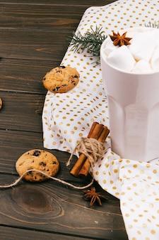 Schale heiße schokolade steht auf dem papier, das mit gewürzen und schokoladenplätzchen bedeckt wird