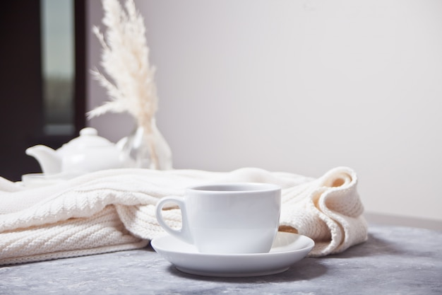 Schale heißer aromakaffee und weißes plaid des knittead und weiße teekanne auf der grauen tabelle